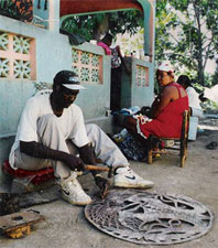 Haitian artist carving an oil drum